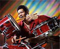 1970s AFRICAN AMERICAN MAN MUSICIAN PLAYING DRUMS STROBE LIGHT EFFECTS BEHIND HIM IN DISCO CLUB Stock Photo - Premium Rights-Managednull, Code: 846-07760722