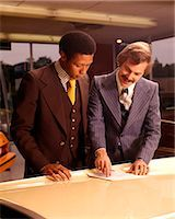 1970s TWO MEN CUSTOMER AND SALESMAN READING SALES CONTRACT ON HOOD OF NEW CAR IN DEALERSHIP SALES SHOWROOM Stock Photo - Premium Rights-Managednull, Code: 846-07760725