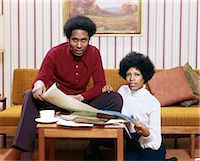 1970s AFRICAN AMERICAN MAN WOMAN COUPLE HUSBAND WIFE LOOKING AT CAMERA EXAMINING NEW HOUSE BLUEPRINTS Stock Photo - Premium Rights-Managednull, Code: 846-07760731