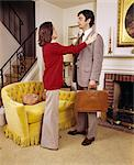 1970s COUPLE WOMAN WIFE ADJUSTING JACKET OF MAN HUSBAND EXECUTIVE READY TO LEAVE FOR WORK