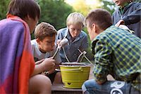 Young boys cooking fish over barbecue Stock Photo - Premium Royalty-Freenull, Code: 649-07760874