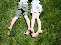 Overhead view of brother and sisters legs as they lay on grass Stock Photo - Premium Royalty-Freenull, Code: 649-07760885