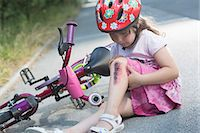 Young girl with injured leg sitting on road with bicycle Stock Photo - Premium Royalty-Freenull, Code: 649-07760998