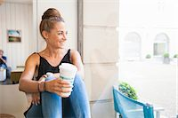 Mid adult woman sitting on window ledge drinking coffee, looking out of window Stock Photo - Premium Royalty-Freenull, Code: 649-07761047
