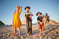 Sister and brothers dressed as native american and cowboys pointing from sand dunes Stock Photo - Premium Royalty-Freenull, Code: 649-07761111