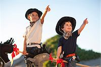 Two brothers dressed as cowboys pointing from sand dunes Stock Photo - Premium Royalty-Freenull, Code: 649-07761114