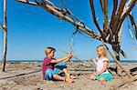 Boy and his sister constructing a circular structure from driftwood, Caleri Beach, Veneto, Italy
