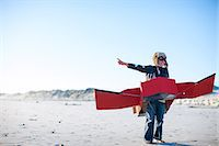 pre-teen beach - Boy standing with toy airplane and pointing on beach Stock Photo - Premium Royalty-Freenull, Code: 649-07761213