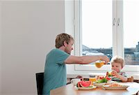 Father and toddler son having breakfast at kitchen table Stock Photo - Premium Royalty-Freenull, Code: 649-07761253