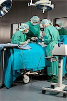 Doctors and nurses operating on a patient in a operating room Stock Photo - Premium Royalty-Freenull, Code: 653-07761287