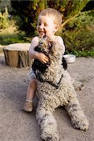 Baby girl playing with Portuguese Water Dog Stock Photo - Premium Royalty-Freenull, Code: 653-07761353