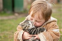 Baby girl holding cat and kissing Stock Photo - Premium Royalty-Freenull, Code: 653-07761358