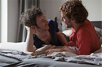 Affectionate gay couple looking at each while relaxing in bedroom Stock Photo - Premium Royalty-Freenull, Code: 653-07761496
