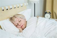 Mature woman sleeping in bed Stock Photo - Premium Royalty-Freenull, Code: 653-07761546