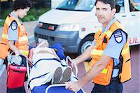 Paramedics wheeling patient on stretcher in hospital parking lot Stock Photo - Premium Royalty-Freenull, Code: 6113-07761969
