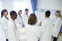 Doctor and residents examining patient in hospital room Stock Photo - Premium Royalty-Freenull, Code: 6113-07761980