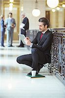 Lawyer doing work on digital tablet in courthouse Stock Photo - Premium Royalty-Freenull, Code: 6113-07762462