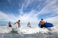 five people - Group of male and female surfer friends wading into sea with surf boards Stock Photo - Premium Royalty-Freenull, Code: 614-07767978