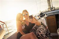people and vacation - Two women on yacht using smartphone Stock Photo - Premium Royalty-Freenull, Code: 614-07768055