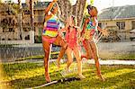 Three girls running and jumping in garden sprinkler