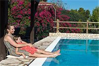Woman with daughter relaxing at swimming pool, Sicily, Italy Stock Photo - Premium Royalty-Freenull, Code: 6102-07768760