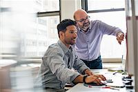 Office life. Two men in an office, using a computer screen. Stock Photo - Premium Royalty-Freenull, Code: 6118-07769528