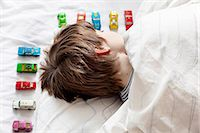 Boy sleeping with toy cars Stock Photo - Premium Royalty-Freenull, Code: 613-07780942