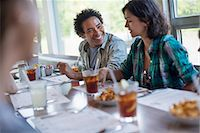 A group of friends eating at a diner. A couple seated side by side. Stock Photo - Premium Royalty-Freenull, Code: 6118-07781804