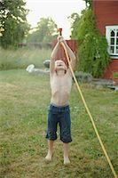 Boy playing with garden hose in garden Stock Photo - Premium Royalty-Freenull, Code: 6102-07790055