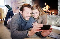 sweater and fireplace - Couple looking at cell phone together Stock Photo - Premium Royalty-Freenull, Code: 6113-07790607