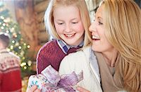 Family exchanging gifts on Christmas Stock Photo - Premium Royalty-Freenull, Code: 6113-07790640