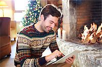 sweater and fireplace - Man using digital tablet in front of fireplace Stock Photo - Premium Royalty-Freenull, Code: 6113-07790665