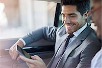 Businessmen looking at cell phone in car Stock Photo - Premium Royalty-Freenull, Code: 6113-07790888