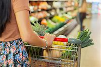 Close up of woman pushing full shopping cart in grocery store Stock Photo - Premium Royalty-Freenull, Code: 6113-07790948