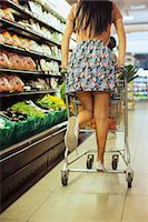 Woman playing on shopping cart in grocery store Stock Photo - Premium Royalty-Freenull, Code: 6113-07791070
