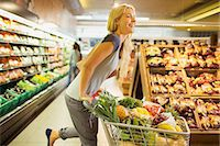 Woman playing with shopping cart in grocery store Stock Photo - Premium Royalty-Freenull, Code: 6113-07791080