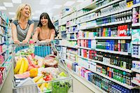 Women pushing full shopping cart together in grocery store Stock Photo - Premium Royalty-Freenull, Code: 6113-07791150
