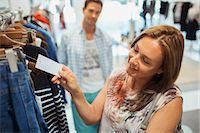 Woman checking tag while shopping in clothing store Stock Photo - Premium Royalty-Freenull, Code: 6113-07791165