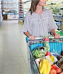 Woman pushing full shopping cart in grocery store