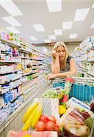 Bored woman pushing full shopping cart in grocery store Stock Photo - Premium Royalty-Freenull, Code: 6113-07791224