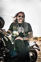 Portrait of mature man sitting on motorcycle on arid plain, Cagliari, Sardinia, Italy Stock Photo - Premium Royalty-Freenull, Code: 649-07803236
