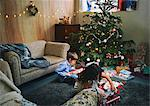 Sister and brother playing with and unwrapping christmas gifts on sitting room floor