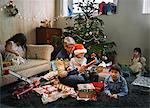Father and four children opening christmas gifts in sitting room
