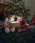 Sister and brother open mouthed on unwrapping glowing christmas gift box