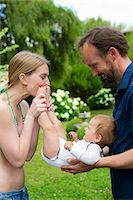 Mother kissing baby daughters feet in garden Stock Photo - Premium Royalty-Freenull, Code: 649-07803426