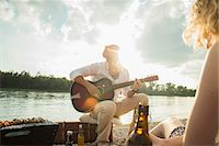 Young man sitting by lake playing guitar Stock Photo - Premium Royalty-Freenull, Code: 649-07804731