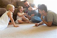 Male couple and two daughters playing on sitting room floor Stock Photo - Premium Royalty-Freenull, Code: 614-07805892