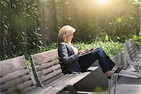 people sitting on bench - Mature businesswoman sitting on bench using laptop Stock Photo - Premium Royalty-Freenull, Code: 614-07805967