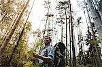 Hiker in forest using digital tablet