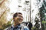 Hiker in forest wearing glasses, smiling